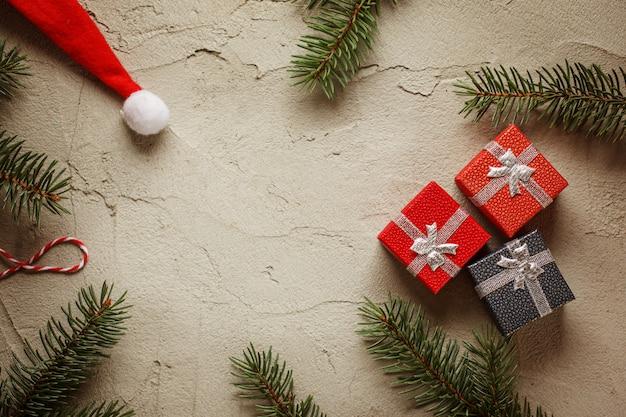 Weihnachtskleine geschenkboxen auf grauem hintergrund mit tannenzweigen. weihnachts- und guten rutsch ins neue jahr-zusammensetzung. ansicht von oben.