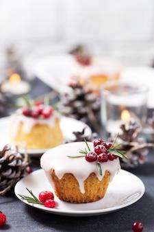 Weihnachtskleiner kuchen mit zuckerglasur, moosbeeren und rosmarin