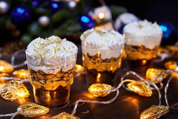 Weihnachtskleinigkeiten in tassen als dessert mit karamell-schneeflocken dekoriert für eine festliche tafel