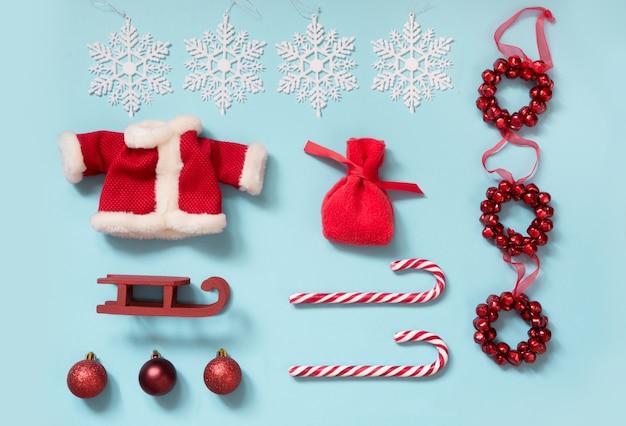 Weihnachtskollektion mit weihnachtsmannsjacke, zuckerstangen, schneeflocken auf blau.