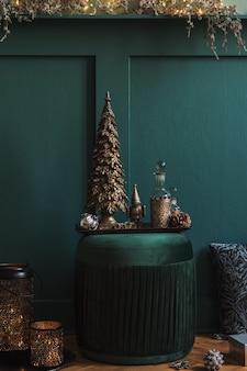Weihnachtskomposition auf dem grünen samtpuff im wohnzimmer. schöne dekoration. weihnachtsbäume, kerzen, sterne, lichter und elegante accessoires. frohe weihnachten und schöne feiertage, vorlage.