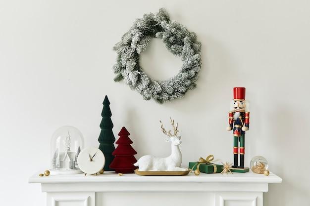 Weihnachtskomposition auf dem weißen kamin im wohnzimmer mit schöner dekoration. weihnachtsbaum und kranz, kerzen, sterne, licht. platz kopieren. vorlage.
