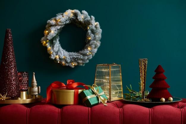 Weihnachtskomposition auf der roten samtbank mit dekoration, geschenken, kranz, laterne und accessoires. platz kopieren. rote und grüne farbe. vorlage.