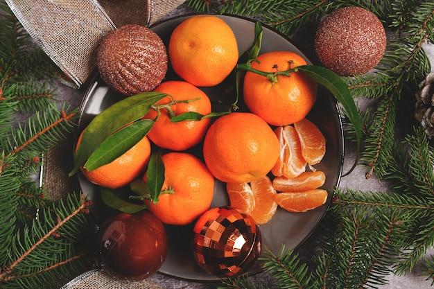 Weihnachtskomposition auf teller mit orangen und tannenbaum, auf grauem hintergrund