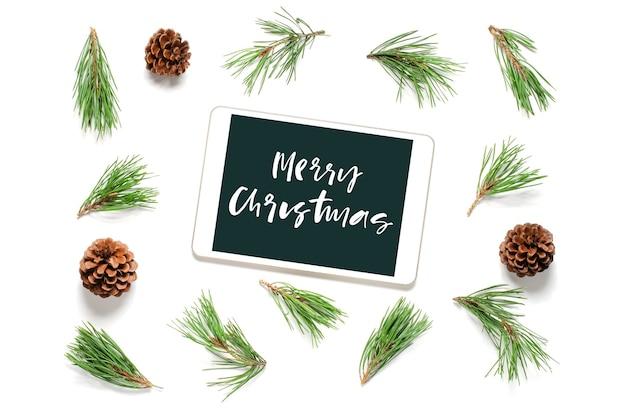 Weihnachtskomposition auf weißem hintergrund. frohe weihnachten handgeschriebene inschrift auf dem gadget-bildschirm. flach liegen.