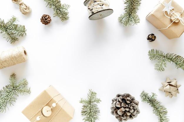 Weihnachtskomposition auf weißer oberfläche. handgemachte geschenkboxen, weihnachtsschmuck, tannenzweige, tannenzapfen. handgemachtes diy-konzept. flache lage, draufsicht, kopierraum