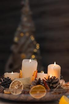 Weihnachtskomposition aus natürlichen materialien und kerzen, im hintergrund ein weihnachtsbaum