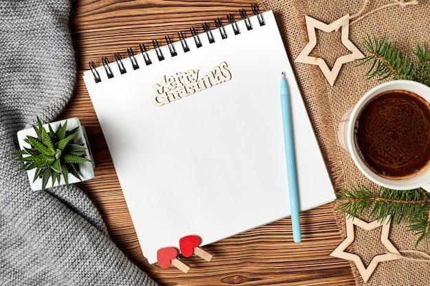 Weihnachtskomposition aus offenem leerem notizblock kaffeetasse schal kaktus und tannenzweigen
