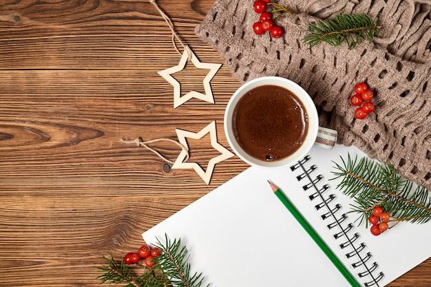Weihnachtskomposition aus offenem leerem notizblock, kaffeetasse, schal und tannenzweigen auf holzhintergrund