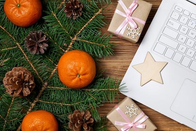 Weihnachtskomposition aus offenem notizbuch, geschenkboxen, tannenzweigen und mandarinen auf holzhintergrund