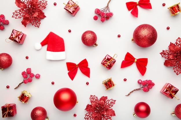 Weihnachtskomposition aus roter weihnachtsdekoration auf grauem hintergrund. flache lage, draufsicht.