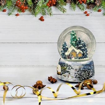 Weihnachtskomposition aus schneekugel, anis und glitzernden haselnüssen auf heller holzoberfläche und hintergrund mit tannenrand. mit kopierraum