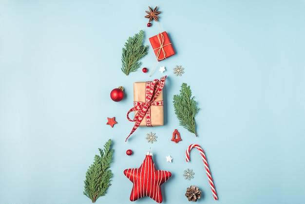 Weihnachtskomposition aus tannenzweigen, dekoration, süßigkeiten, beeren und geschenkboxen auf blauem hintergrund