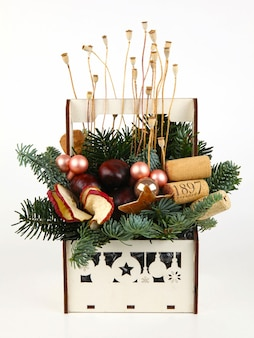 Weihnachtskomposition aus tannenzweigen, weinkorken, kugeln, getrockneten apfelscheiben, mohn und kastanien. in weißer holzkiste. auf weißem hintergrund