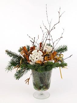 Weihnachtskomposition aus tannenzweigen, zimt, dekorativen schneeflocken, band und silbernen schokoriegeln. in schlichter glasvase. auf weißem hintergrund