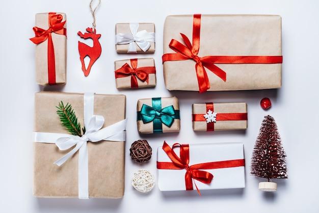 Weihnachtskomposition aus verschiedenen geschenkboxen, die in kunsthandwerk und weißes papier eingewickelt und mit satinroten bändern verziert sind. draufsicht, flach liegen.