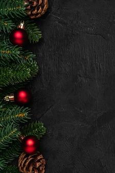Weihnachtskomposition. bunte verzierung, tannenzapfen und tannennadeldekorationen auf dunklem hintergrund. kopierbereich der draufsicht