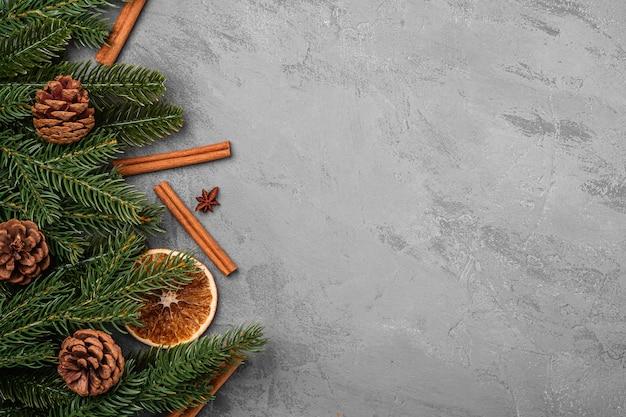 Weihnachtskomposition. dekorationen von zimt, anis, getrockneten früchten, tannenzapfen und tannennadeln auf grauem hintergrund. kopierbereich der draufsicht