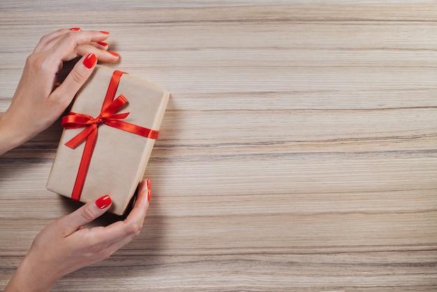Weihnachtskomposition. draufsicht, flach liegen. weibliche hände halten geschenkbox in bastelpapier gewickelt und mit rotem satinband auf holztisch verziert