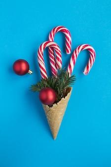 Weihnachtskomposition. eistüte mit karamellstangen, roten kugeln und fichtenzweigen auf der blauen oberfläche. lage vertikal. speicherplatz kopieren. draufsicht.