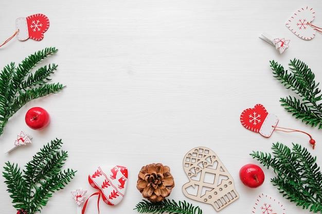 Weihnachtskomposition. feld gemacht von den weihnachtsgeschenken, kiefernniederlassungen, spielwaren auf weißem backgro