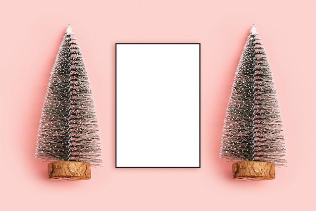 Weihnachtskomposition. fotorahmen, draufsicht des kiefernweihnachtsbaumpastellrosa-hintergrundes, c