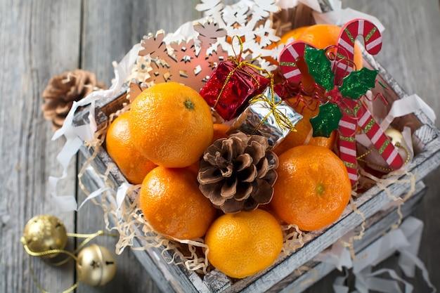 Weihnachtskomposition. frische mandarinen und neujahrsspielzeug in einer kiste auf der alten holzoberfläche. rustikaler stil. selektiver fokus.