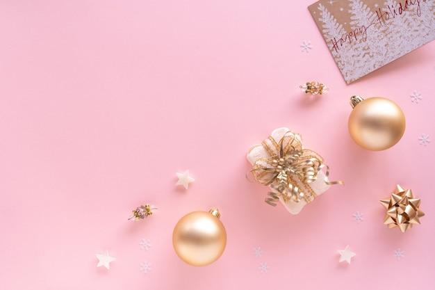 Weihnachtskomposition. geschenk, kugeln, grußkarte, goldene verzierungen auf pastellrosa oberfläche. weihnachts-, winter-, neujahrskonzept. flache lage, draufsicht, kopierraum von oben.