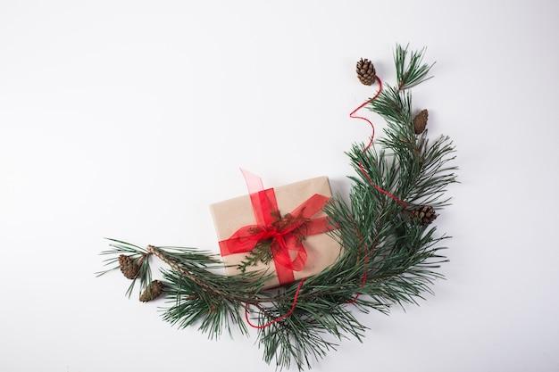 Weihnachtskomposition. geschenk, weihnachtsdekoration, zypressenzweige, tannenzapfen auf weißem hintergrund