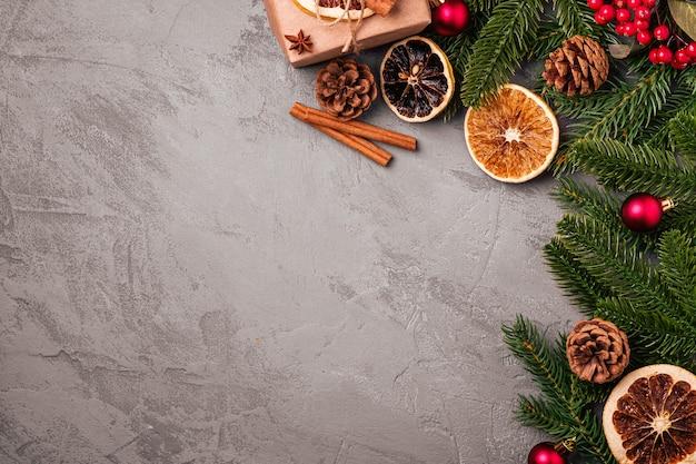 Weihnachtskomposition. geschenkbox, kugeln, zimt, anis, getrocknete früchte, tannenzapfen und tannennadeldekorationen auf grauem hintergrund. kopierbereich der draufsicht