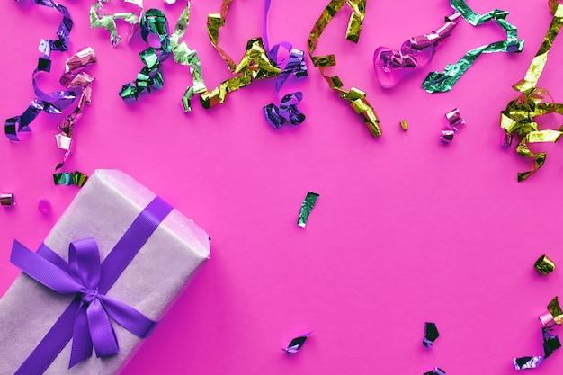 Weihnachtskomposition. geschenkbox mit band- und konfettidekorationen auf buntem hintergrund des pastellpapiers. weihnachts-, winter-, neujahrsfeierkonzept