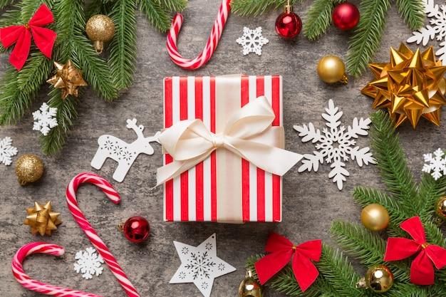 Weihnachtskomposition. geschenkbox mit dekorationen des neuen jahres auf farbigem hintergrund. weihnachten, winter, neujahrskonzept. flache lage, ansicht von oben, kopienraum.