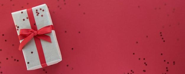 Weihnachtskomposition. geschenkbox mit rotem band und konfetti-dekorationen auf buntem hintergrund des pastellpapiers. flache lage, draufsicht, kopierraum