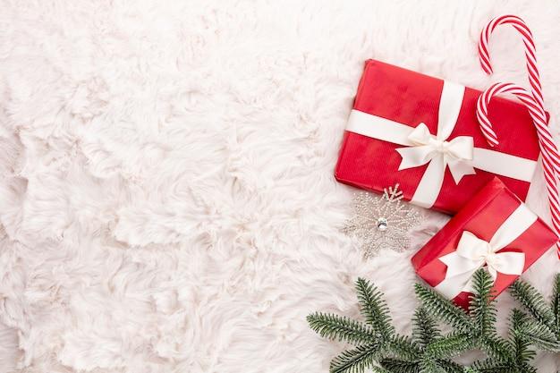 Weihnachtskomposition. geschenkbox, weihnachtsschmuck auf wollhintergrund. flache lage, ansicht von oben, kopienraum.