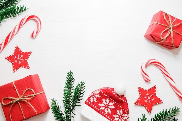 Weihnachtskomposition. geschenke, tannenbaumaste, rote dekorationen auf weißem hintergrund.