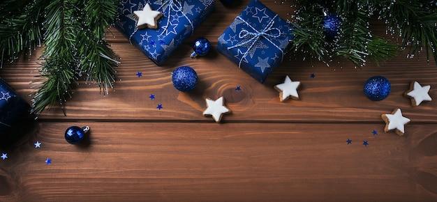 Weihnachtskomposition. geschenke, tannenzweige, blaue verzierungen auf holzoberfläche. weihnachts-, winter-, neujahrsfeiertagskonzept. flache lage, draufsicht, kopierraum, langes banner