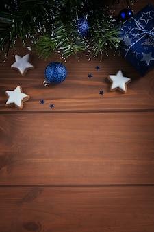 Weihnachtskomposition. geschenke, tannenzweige, blaue verzierungen auf holzoberfläche. weihnachts-, winter-, neujahrsfeiertagskonzept. flache lage, draufsicht, kopierraum