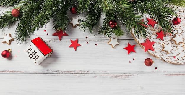 Weihnachtskomposition. geschenke, tannenzweige, rote verzierungen auf weißem holz. weihnachts-, winter-, neujahrsfeiertagskonzept. flache lage, draufsicht, kopierraum, langes banner