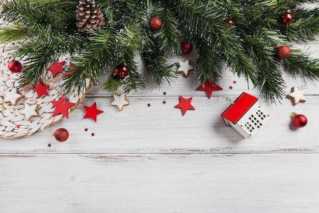 Weihnachtskomposition. geschenke, tannenzweige, rote verzierungen auf weißem holz. weihnachts-, winter-, neujahrsfeiertagskonzept. flache lage, draufsicht, kopierraum