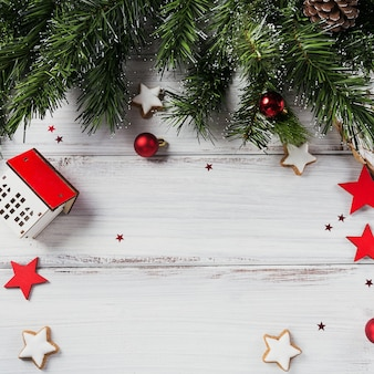 Weihnachtskomposition. geschenke, tannenzweige, rote verzierungen auf weißer holzoberfläche. weihnachts-, winter-, neujahrsfeiertagskonzept. flache lage, draufsicht, kopierraum