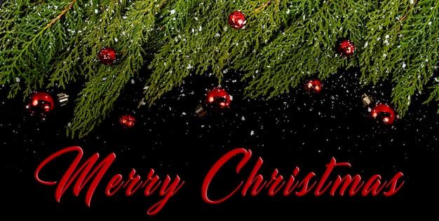 Weihnachtskomposition. girlanda mit roten weihnachtskugeln und schnee auf schwarzem hintergrund