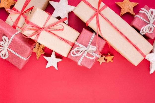 Weihnachtskomposition, grußkarte. rote weihnachtsdekorationen, sterne und geschenkboxen auf rotem hintergrund. flache lage, draufsicht, platz für den text