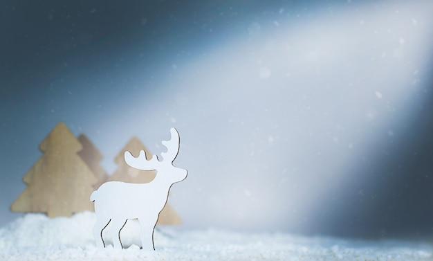 Weihnachtskomposition. hirsch in der nähe des waldes unter schneefall.