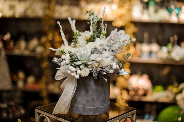 Weihnachtskomposition in der grauen schachtel mit weißen orchideen, saftigen und verschiedenen ornamenten