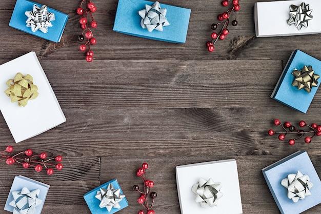 Weihnachtskomposition, in einem kreis sind geschenkboxen mit goldenen und silbernen schleifen und zweigen mit roten beeren.