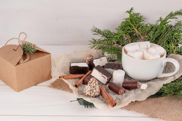 Weihnachtskomposition kakao mit marshmallows auf einem weißen hintergrund zweige eines weihnachtsbaums