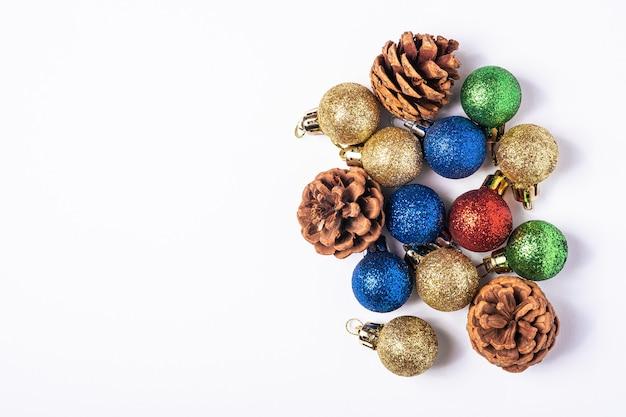 Weihnachtskomposition mit bunten kugeln, tannenzapfen und verzierungen dekorationen auf weißem hintergrund