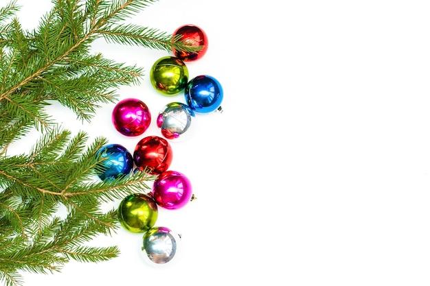 Weihnachtskomposition mit bunten kugeln und tannenzweigen. dekorationen des neuen jahres auf weißem hintergrund. mockup-grußkartenvorlage, flach, ansicht von oben