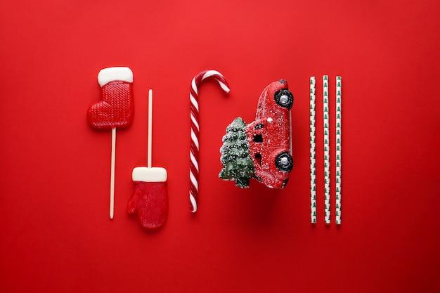 Weihnachtskomposition mit einem roten auto auf rot. flache zusammensetzung.