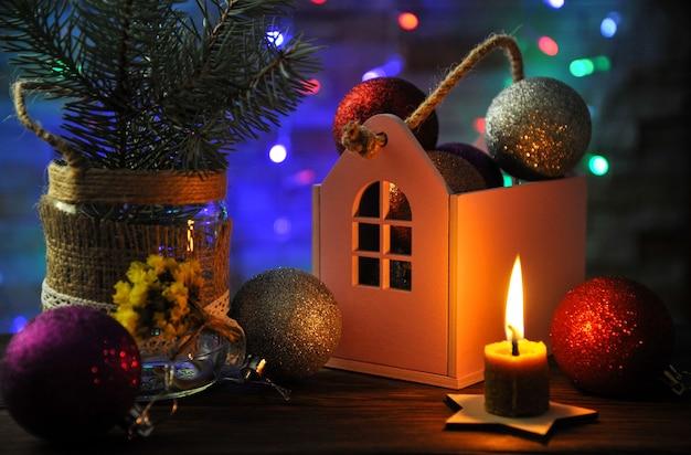Weihnachtskomposition mit einer brennenden kerze, einem haus und weihnachtsdekorationen auf einem tisch